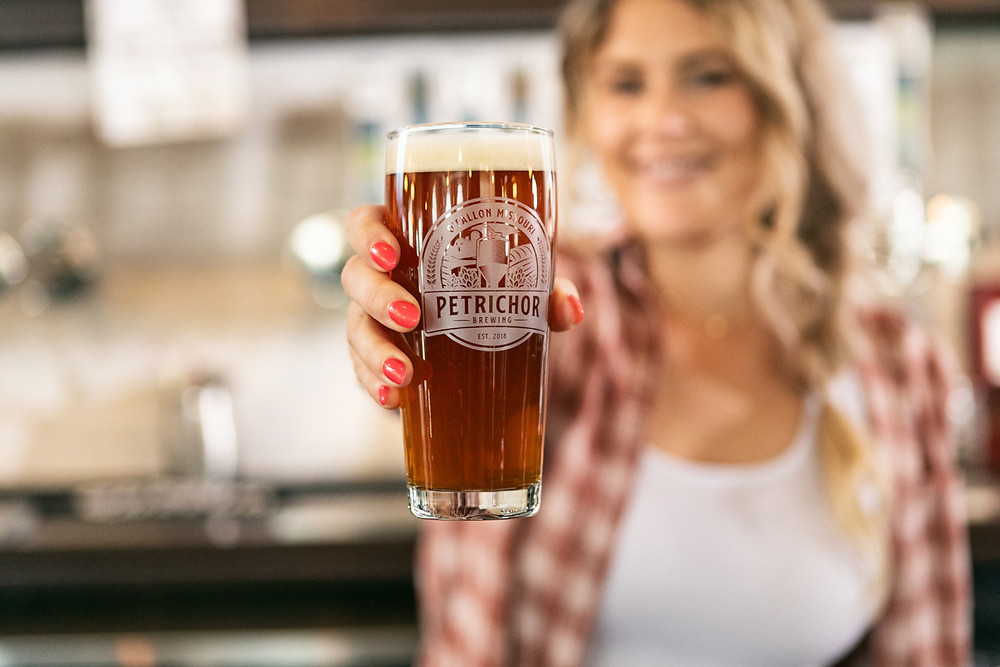a customer holds up a pint of Petrichor Brewing Company beer