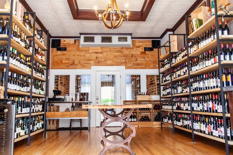 A retail wine shop with shelves lined with wine and wooden decor
