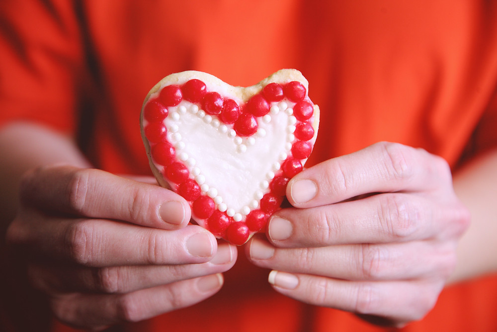 Hands hold up a heart-shaped cookie