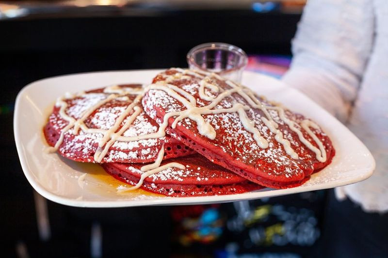 Waiter holds up a plate of red velvet pancakes from Square Cafe