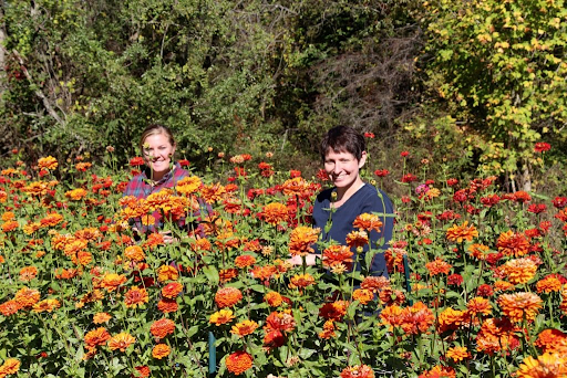 Jodi and an employee at Cherry Valley Organics in a flower field