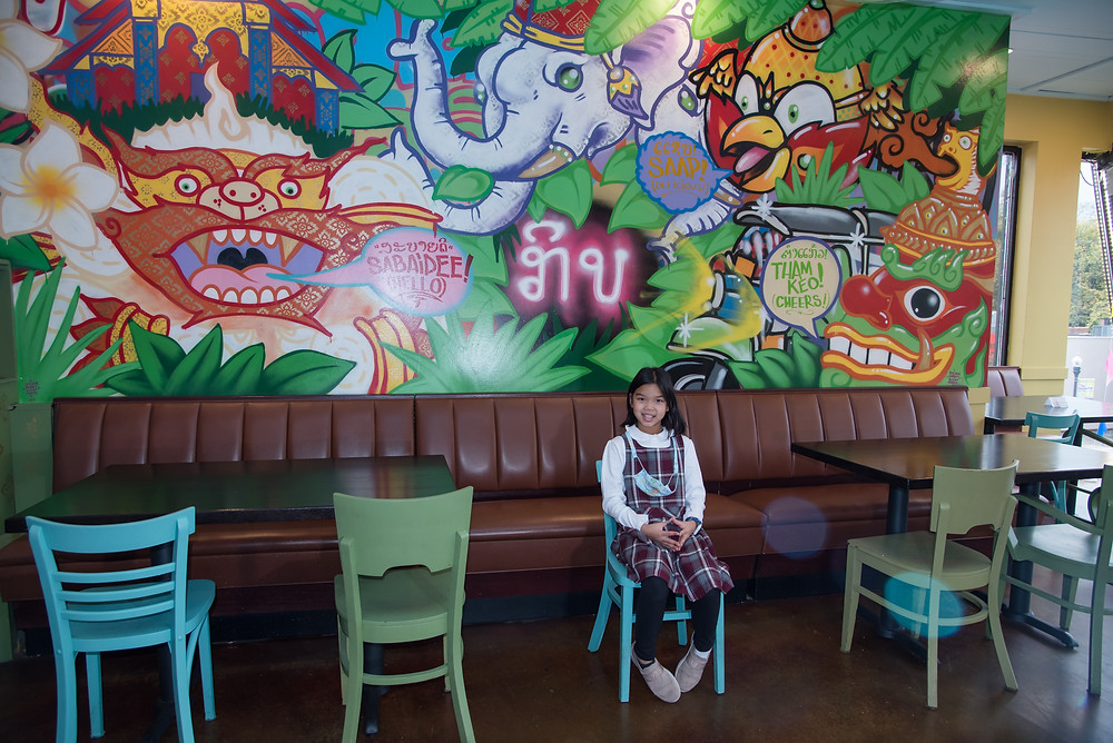 One of Nor's young daughters poses in front of the graffiti art wall at Kiin