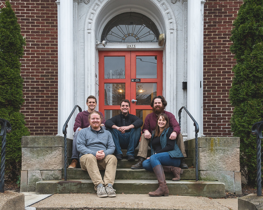 The five owners of Back Alley Brewing Company sit on the brewery's steps