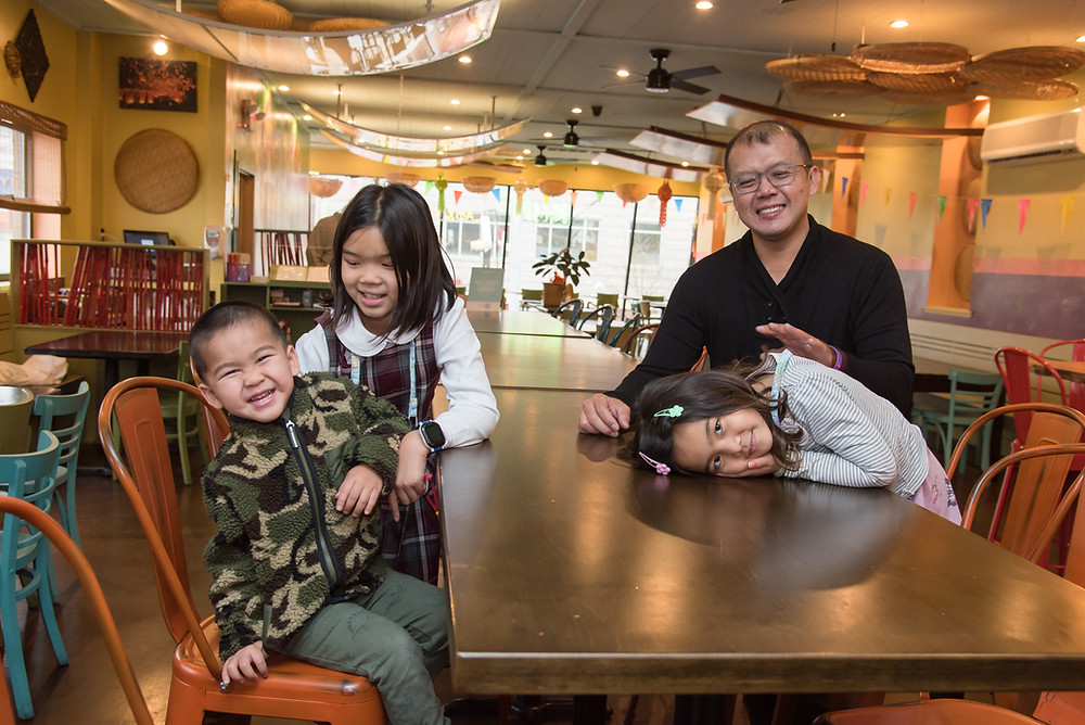 Norraset Nareedokmai, owner of Kiin Lao and Thai Eatery, sits at a table in the restaurant with his three children