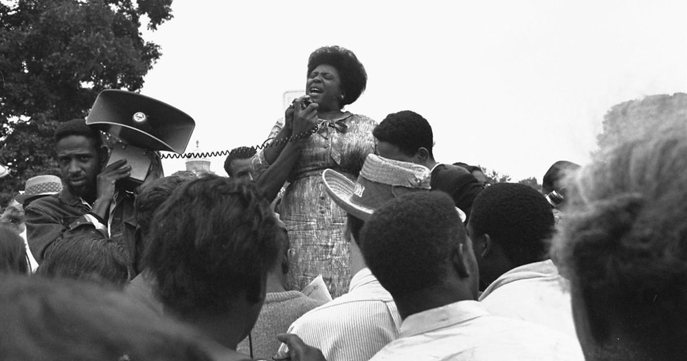 Fannie Lou Hamer speaks to a crowd of people from a megaphone