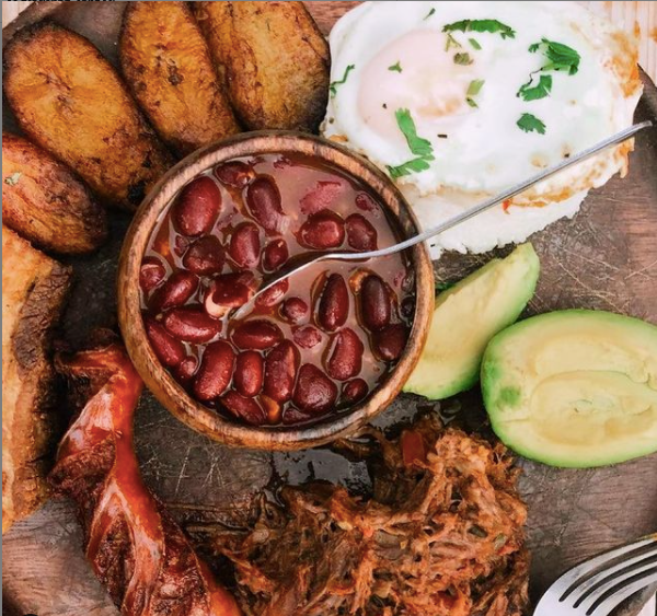 a plate of frijoles, plantains, avocado, and meat from Barroco in Cleveland