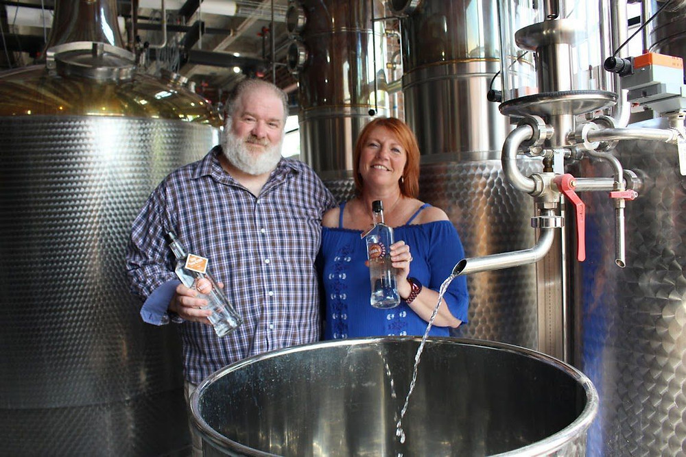 Kevin and Ann Thomas, owners of Western Reserve Distillers, hold bottles of their spirits in the distillery