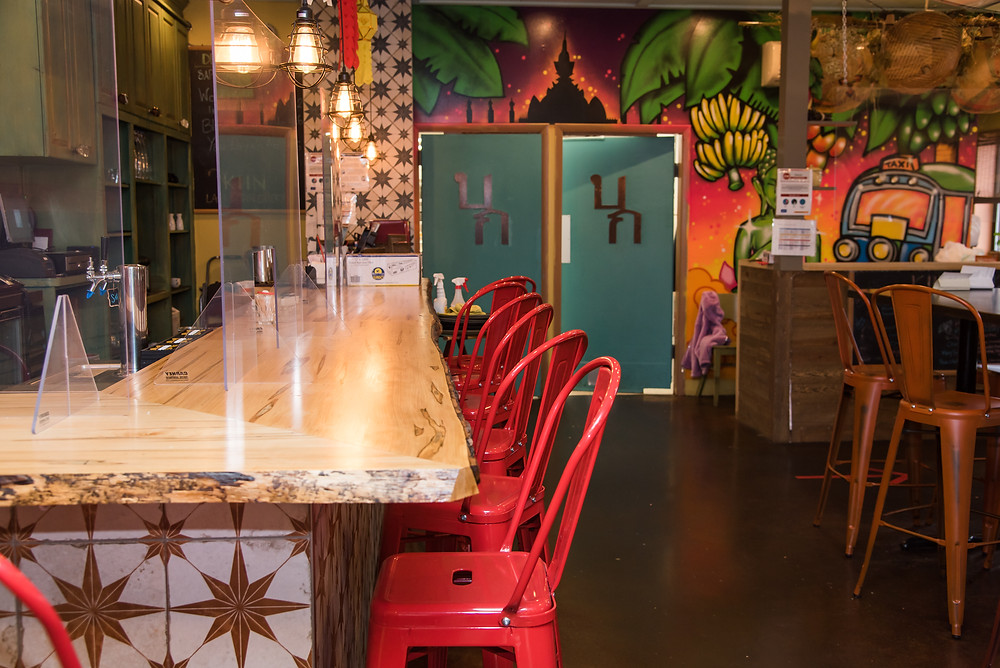 Interior of Kiin Lao and Thai Eatery in Pittsburgh, featuring the bar area and red chairs