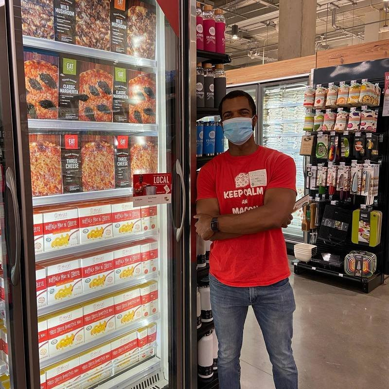 Myles Powell in front of 8Myles products in a Whole Foods