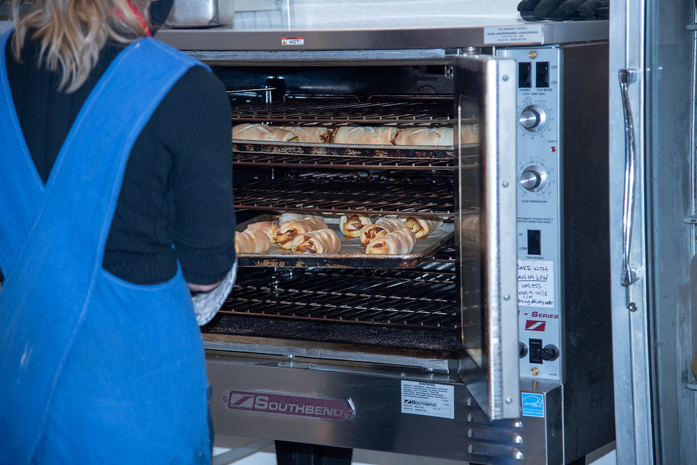 baker takes a tray of pepperoni rolls out of a conventional oven