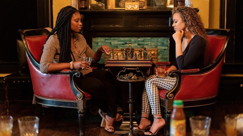 Two women play chess in a classy room while enjoying Guidance Whiskey