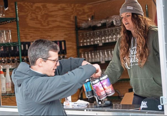 Customer purchases a pack of beer from the Grist House Brewery walk-up window