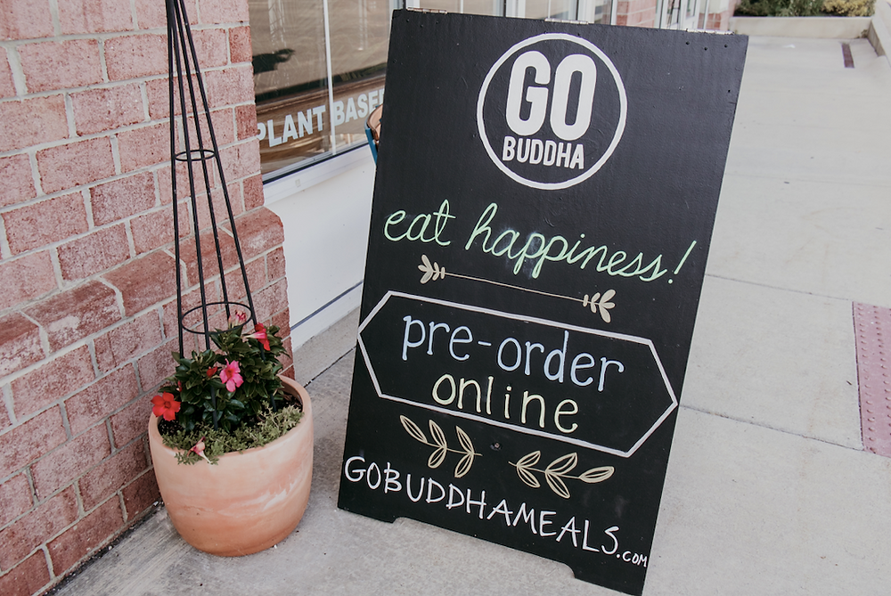 "a folding chalkboard for Go Buddha outside restaurant that reads ""Eat Happiness! Pre-Order Online!"""