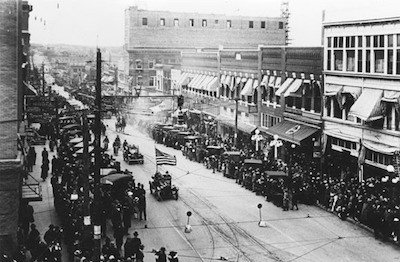 Black and white photo of people lining the streets of Greenwood