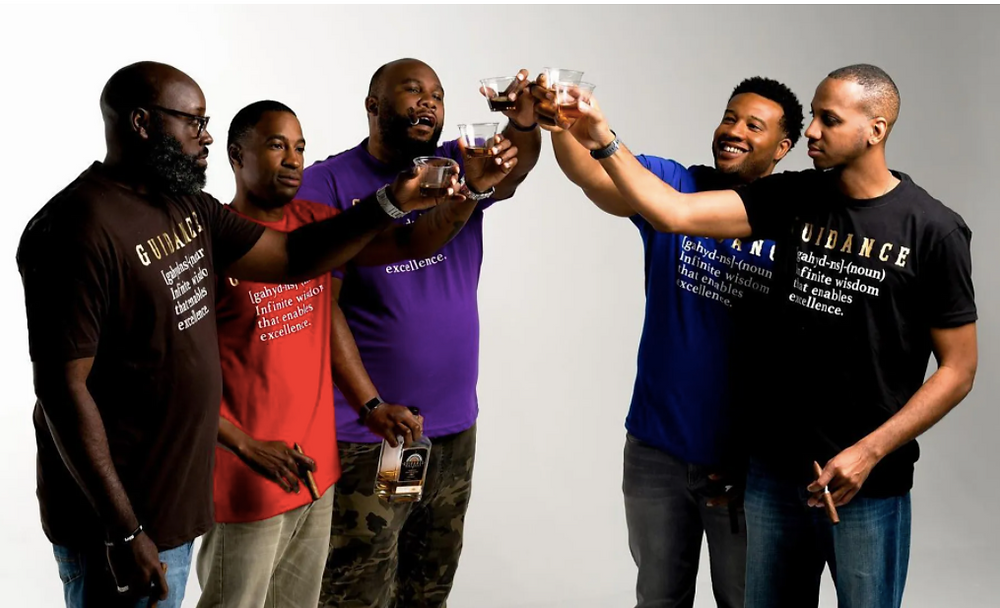 A group of five Black men with cigars and whiskey clink their glasses