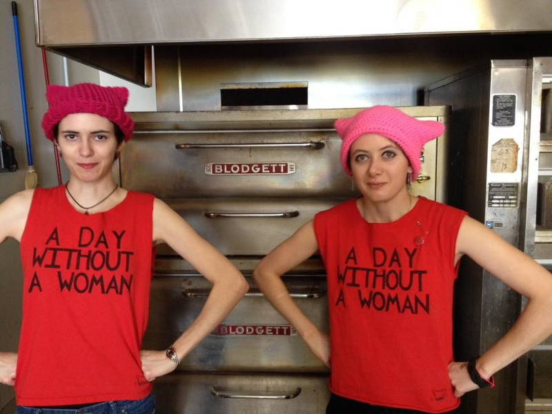 """Two of the owners of Bakery on the Square pose with hands on hips wearing shirts that read """"A Day Without A Woman"""""""