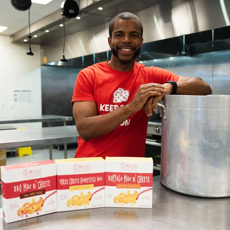 Myles Powell, owner of 8Myles poses with three of his mac and cheese flavors in an incubator kitchen