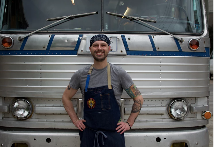 Luke Cypher, owner of Blue Sparrow food truck in Pittsburgh, in front of his renovated Greyhound food bus