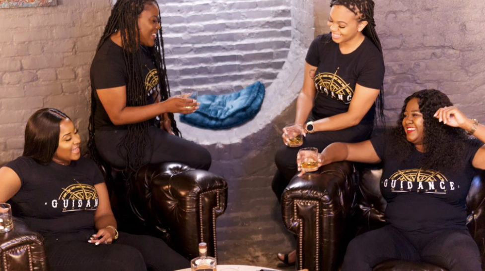 Four women in Guidance Whiskey t-shirts lounge with glasses of whiskey