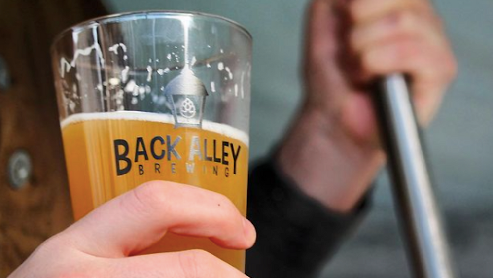 Someone holds a pint glass marked with the Back Alley Brewing logo
