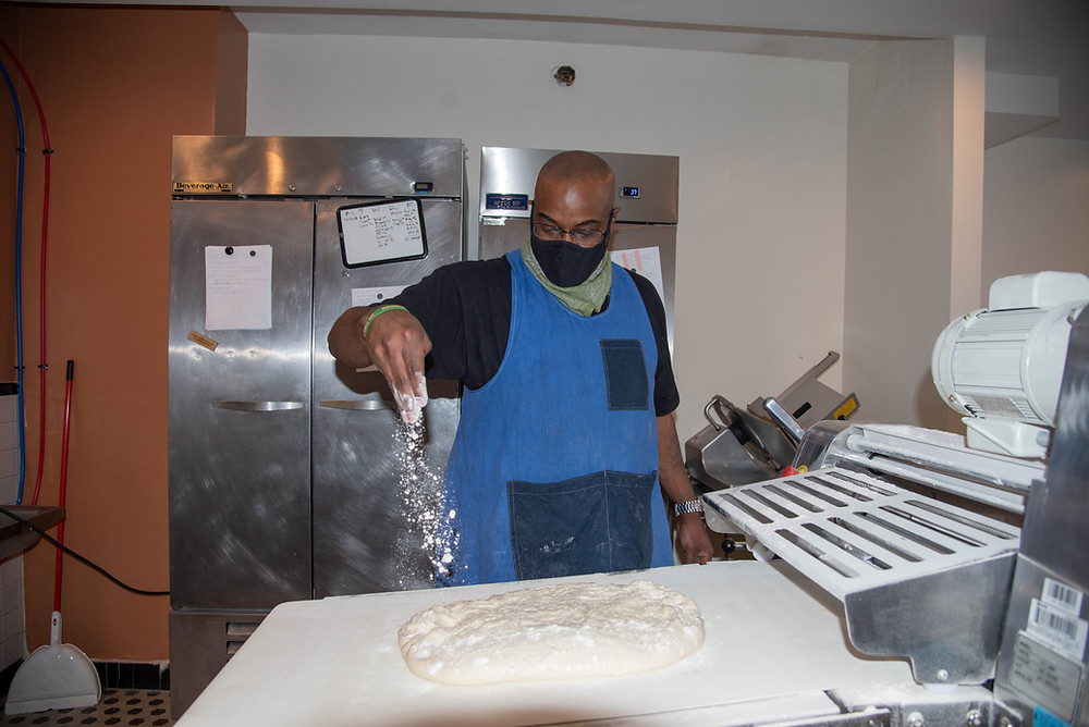 A baker sprinkles flour on dough at Rolling Pepperoni, a Pittsburgh bakery and Honeycomb alum