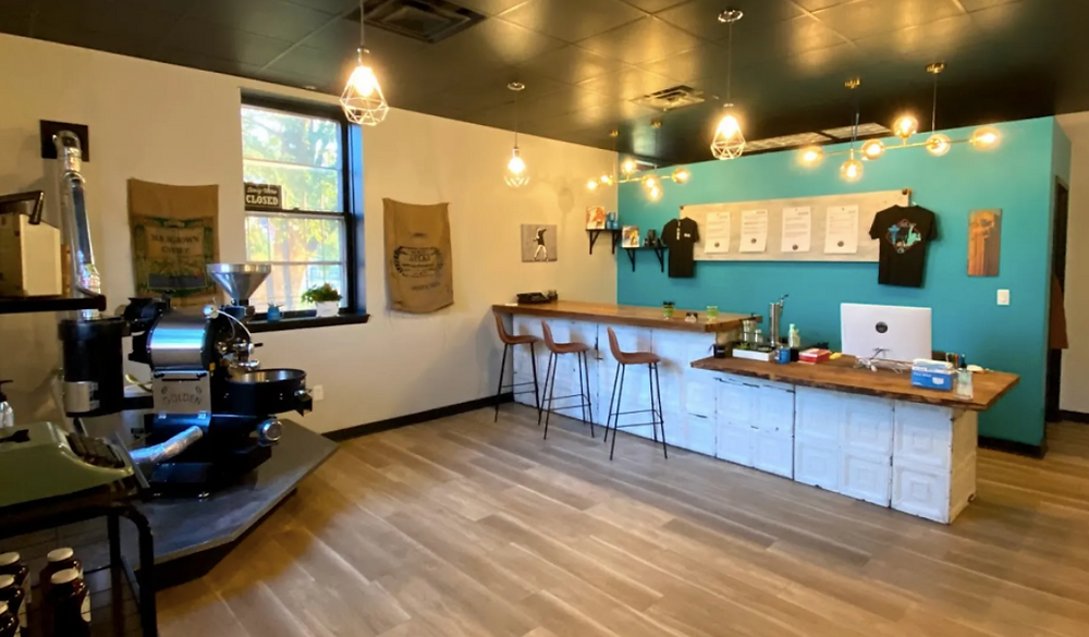 The interior of Scoot! Cold Brew in Cleveland, which features a blue wall and coffee machinery