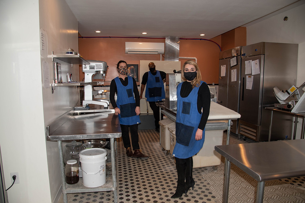 The crew at Rolling Pepperoni in Pittsburgh stand in their bakery kitchen wearing masks and matching aprons