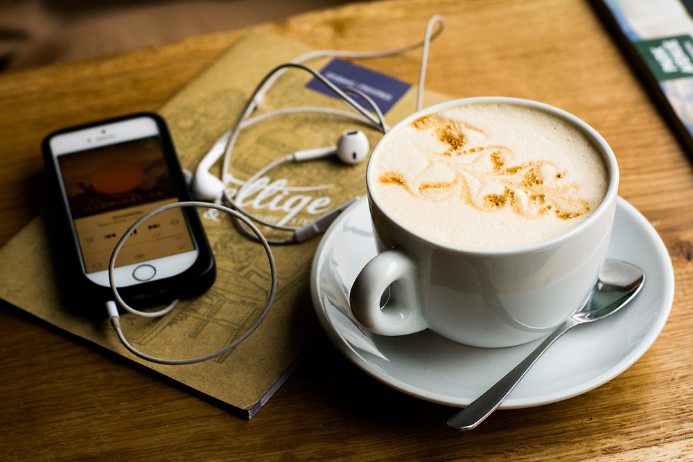 A latte next to a phone with headphones attached