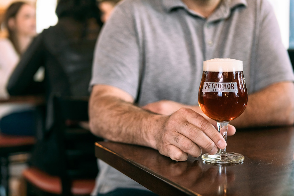 a customer sits with a glass of Shortleaf Brewing Company beer