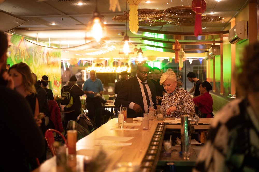 Numerous groups of people stand at the bar and tables at Kiin, surrounded by the decor and lights