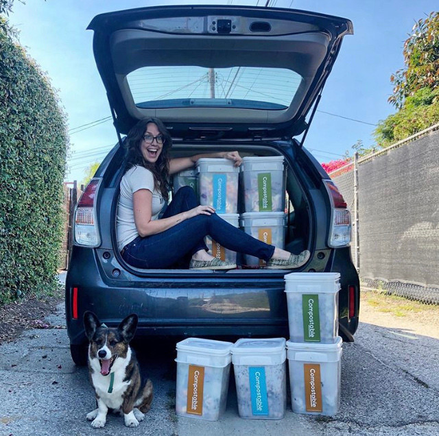 Monique, owner of Compostable LA, poses in the back of the Prius with which she transports compost pick-ups across LA