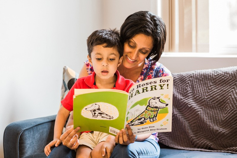 Priya, owner of Flexable, reads a picture book to her young son