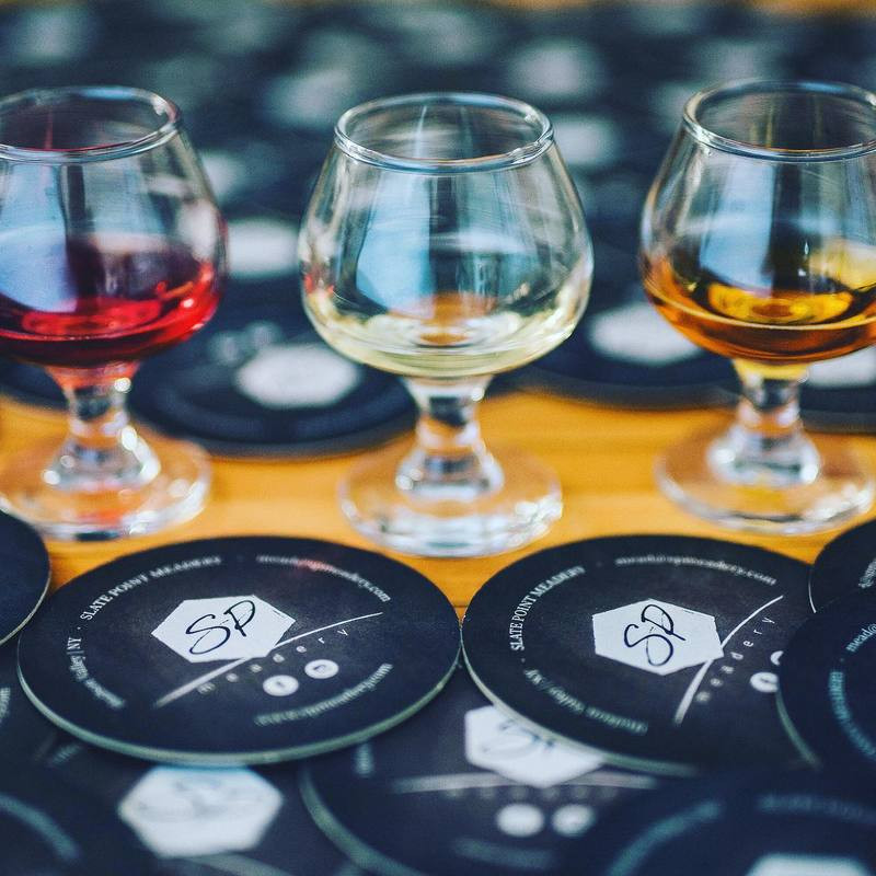 Sampler glasses of mead and coasters with the Slate Point Meadery logo