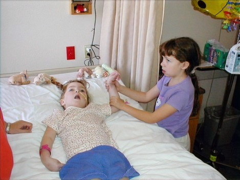 Caitlin, at 7 years old, moving Morgan's arm, while Morgan lays in her hospital bed