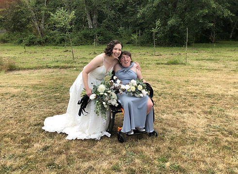 Caitlin in her wedding dress putting her arm around her sister, who is in a bridesmaid dress, both are holding flowers and smiling at the camera