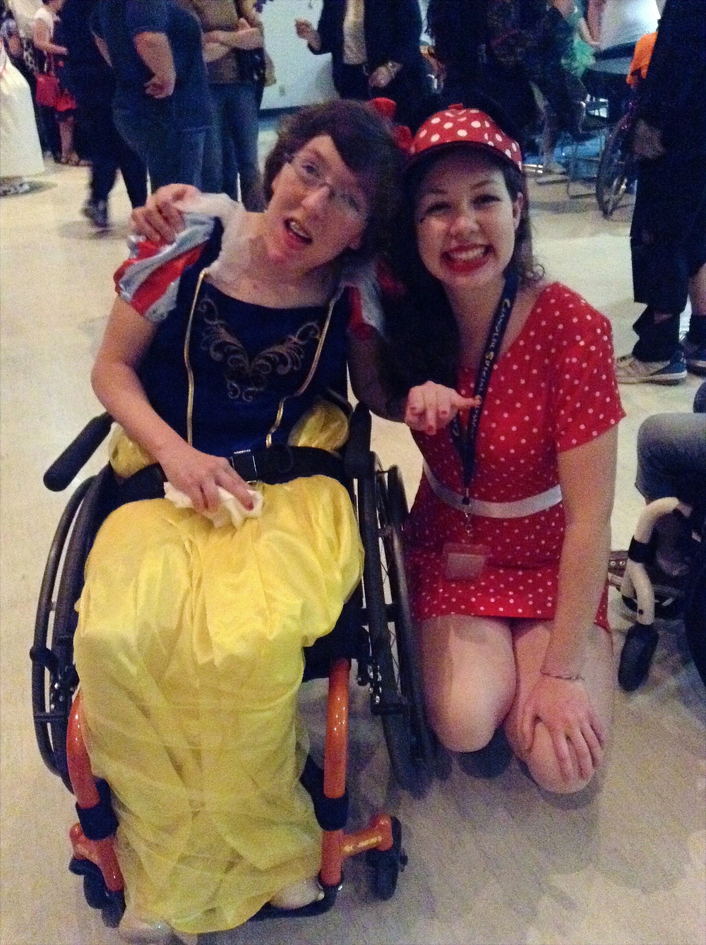Morgan is wearing a Snow White outfit while sitting in her wheelchair. Caitlin is kneeling next to her wearing a Minnie Mouse outfit.