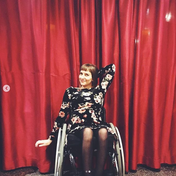 Rebekah is posing with on arm behind her head and one arm at her side while wearing a black, floral dress. She is sitting in her wheelchair in front of a red stage curtain.