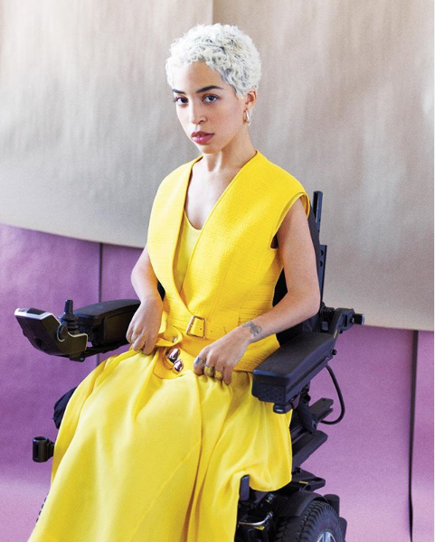 Jillian is sitting in her power wheelchair in a bright yellow dress facing the camera.