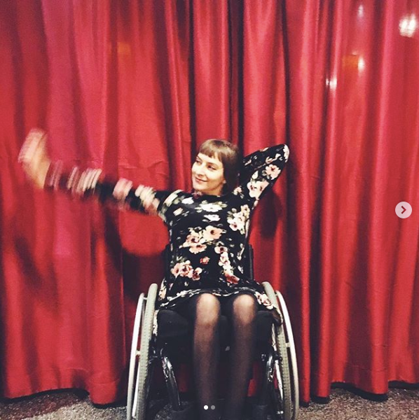 Rebekah is posing with her arm out to the side while wearing a black, floral dress. She is sitting in her wheelchair in front of a red stage curtain.