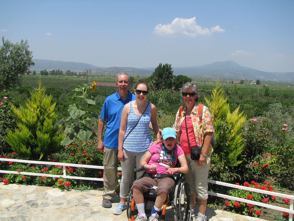 Caitlin, her parents, and her sister are in the foreground looking at the camera. In the background there are lush green fields and hills.