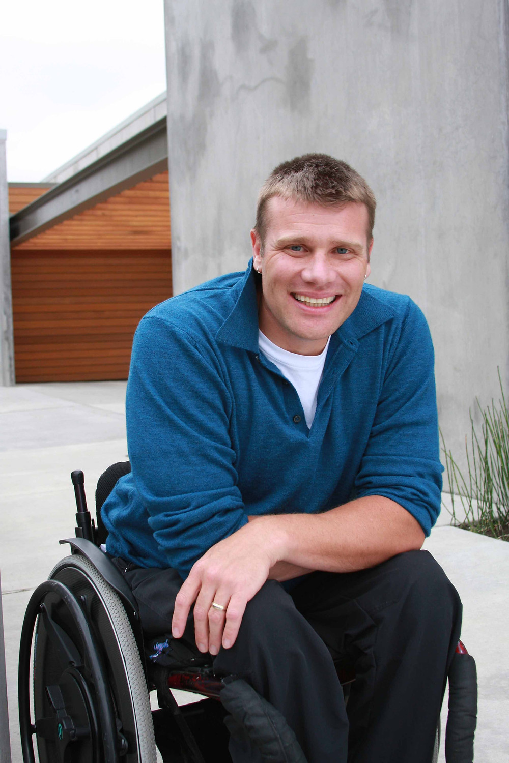 Barry sitting in his wheelchair in front of a modern, concrete house