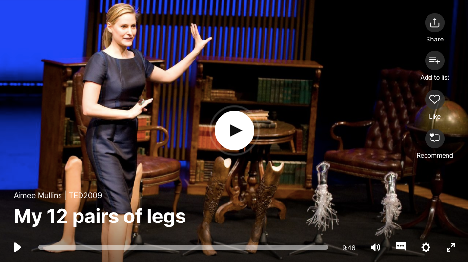 Screenshot from Aimee's TED Talk, My 12 pairs of legs, image shows Aimee motioning to prosthetic legs on stage with her