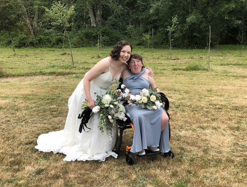 Morgan and Caitlin dressed up for Caitlin's wedding, both holding bouquets of flowers and smiling at the camera with their arms around each other.