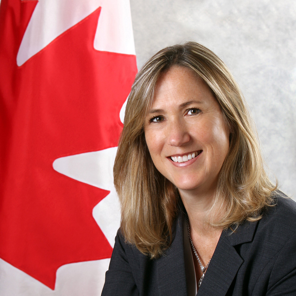 Ms. Kirsten Hillman, Canada's Deputy Ambassador to the US, beside a Canadian flag