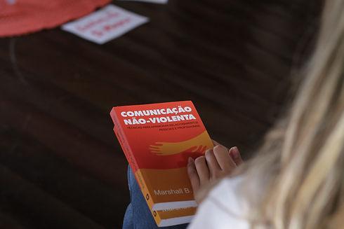 FOTO DE UMA MULHER SEGURANDO O LIVRO COMUNICAÇÃO NÃO VIOLENTA, DE MARSHALL ROSENBERG.