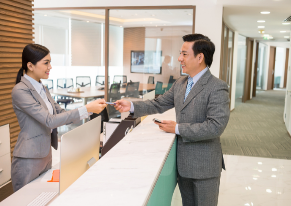 receptionist giving electronic key card to business man