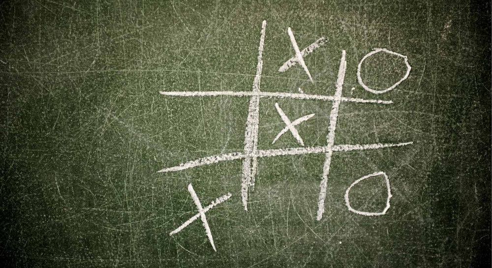 Tic Tac Toe game on a board written by chalk