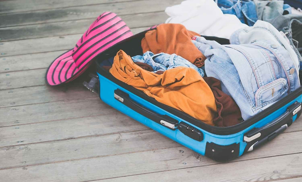 Luggage with messy clothes in it, packing cubes needed
