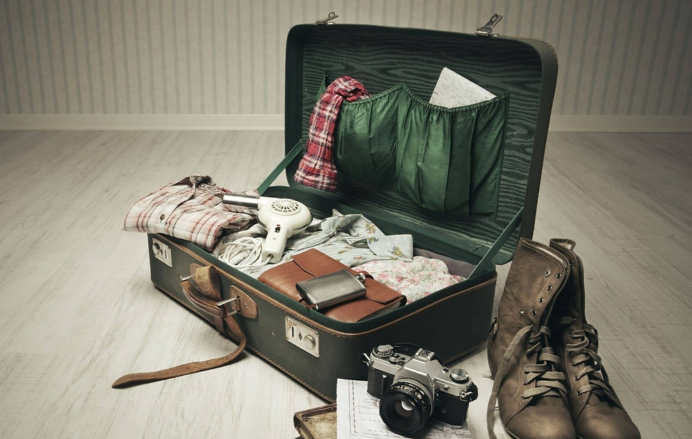 Unorganised luggage, vintage style suitcase with hairdryer in it, old flask, dairy, boots are standing next to the suitcase