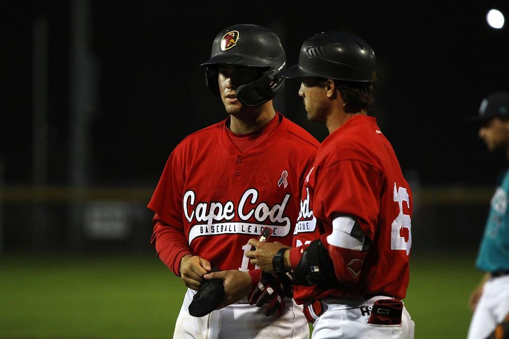 Garret Guillemette talks to coach Ryan Erickson at first base